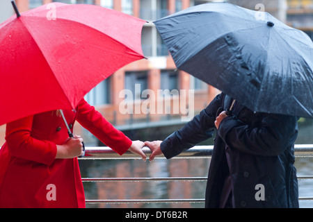 Symmetrical couple holding handrail and carrying umbrella's - Stock Photo