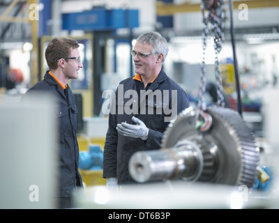 Engineer and apprentice in discussion next to gear wheel at work station in factory - Stock Photo