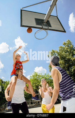 Group of friends having fun playing basketball - Stock Photo