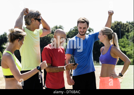 Mature trainer celebrating timing with group of adults - Stock Photo