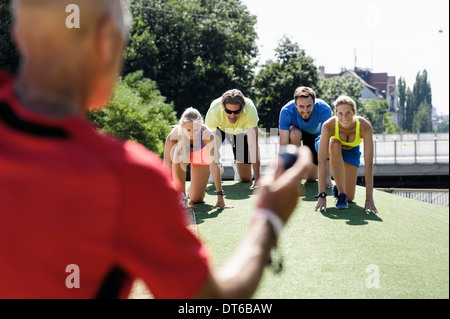 Mature man training a group of adult runners at start line - Stock Photo