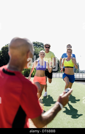 Mature man training a group of adult runners - Stock Photo