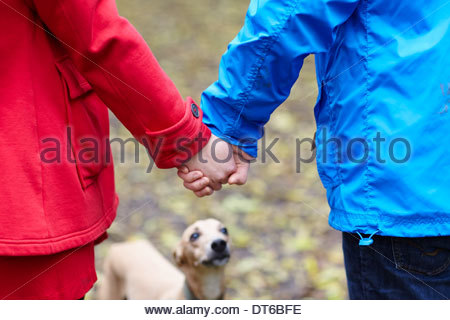 Cropped image of young couple and whippet - Stock Photo