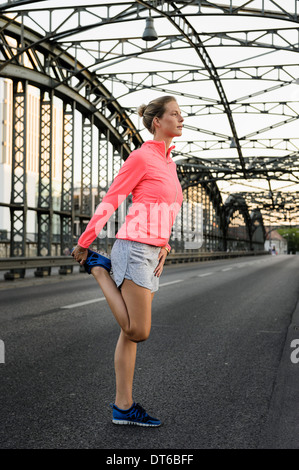 Young female runner stretching on bridge - Stock Photo