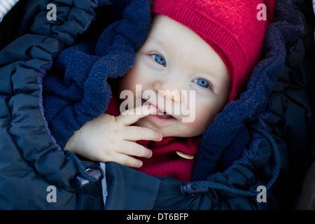 Portrait of baby girl in sleeping bag wearing hat - Stock Photo
