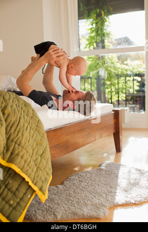 Father lifting baby daughter on bed - Stock Photo