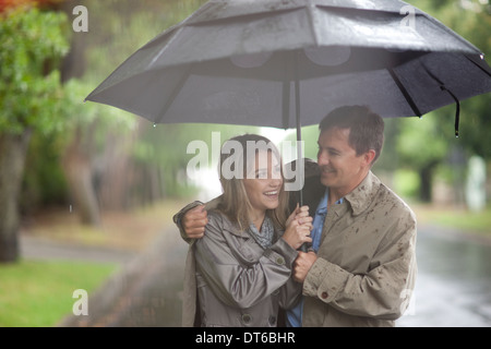 Young woman and mature man walking in rainy park - Stock Photo