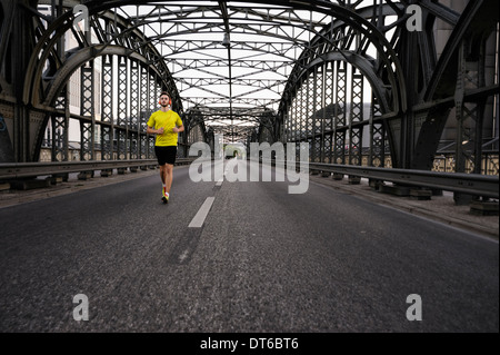Young male athlete running on bridge - Stock Photo