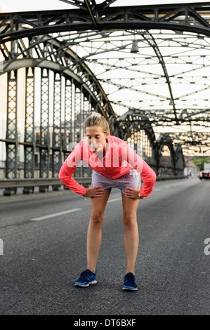 Young female runner preparing for run on bridge - Stock Photo