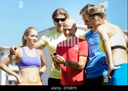 Mature male trainer and a group of adult runners - Stock Photo