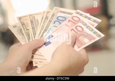 Female hands holding American, British and European bank notes - Stock Photo