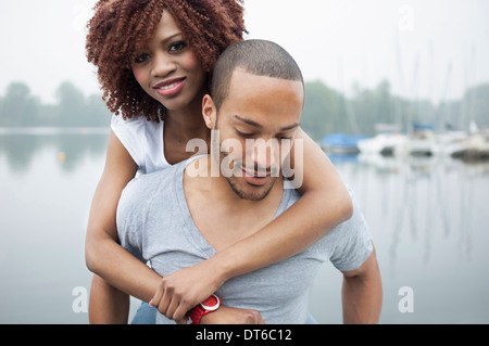 Portrait of young man giving woman piggyback - Stock Photo