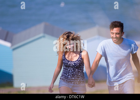 Young couple holding hands with beach huts in background