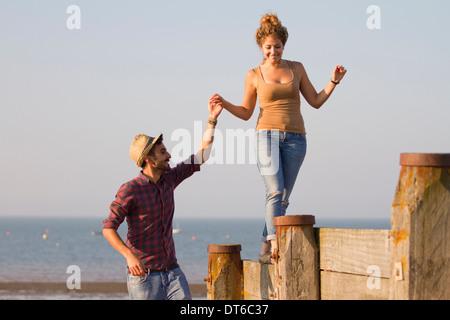 Young woman balancing on groynes holding man's hand - Stock Photo