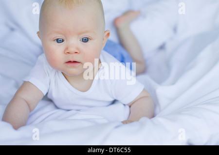 Baby girl lying on bedclothes - Stock Photo
