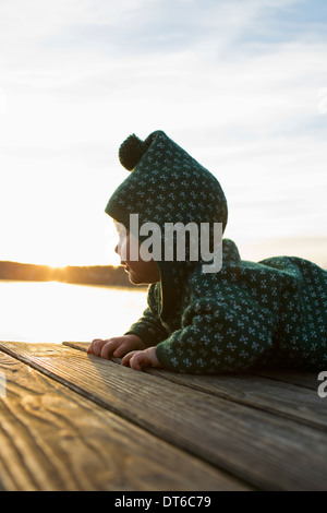 Baby girl crawling on jetty - Stock Photo