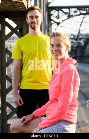 Portrait of young male and female runners on bridge - Stock Photo