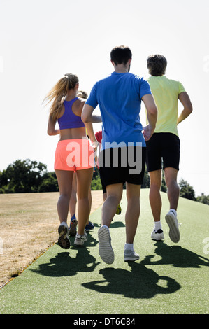 Mature trainer running with group of adults in park - Stock Photo