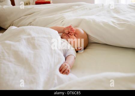 Baby girl asleep on bed - Stock Photo