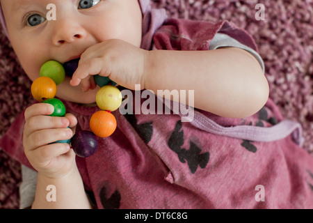 Baby girl with teething toy - Stock Photo