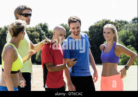 Mature male trainer and a group of adult runners looking at stopwatch - Stock Photo