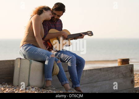 Young couple on beach, man playing guitar - Stock Photo