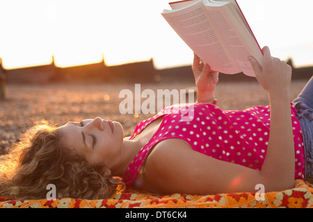Young woman lying on beach reading book
