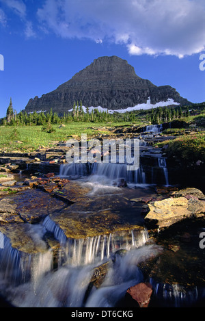 The landscape of Glacier National Park, to Mount Reynolds peak, and Logan Pass. Water flowing over rocks. - Stock Photo