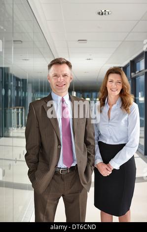 Portrait of business colleagues in corridor - Stock Photo