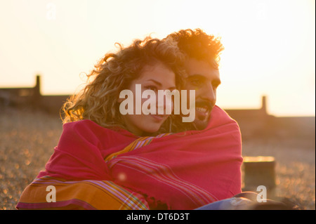 Young couple wrapped in towel on beach - Stock Photo