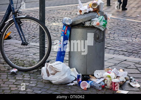 Overfull rubbish bin with trash around and garbage piled on top in city street - Stock Photo