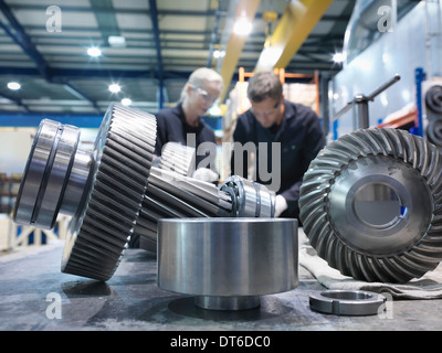 Male and female engineers assembling industrial gearbox in engineering factory - Stock Photo