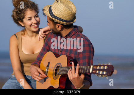Young couple, man playing guitar - Stock Photo