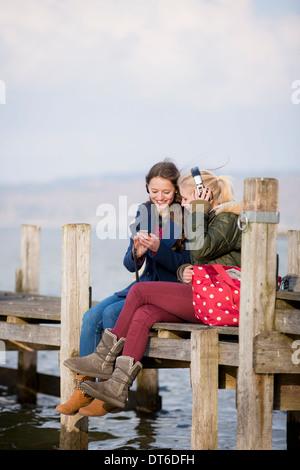 Teenage girls sitting on jetty listening to music - Stock Photo