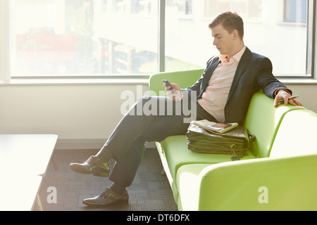 Businessman in departure lounge using cell phone - Stock Photo