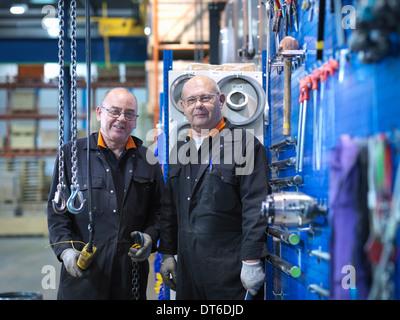 Mature engineers working in engineering factory, portrait - Stock Photo