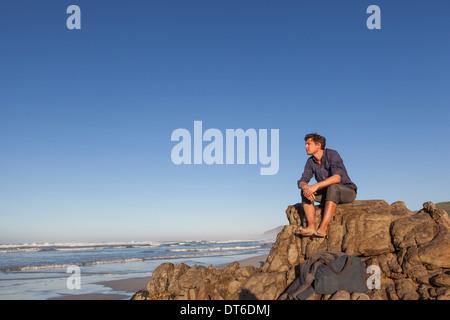 Man sitting on rock at seaside - Stock Photo