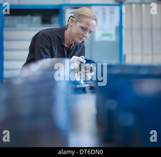 Female engineer assembling small parts of industrial gearbox in engineering factory - Stock Photo
