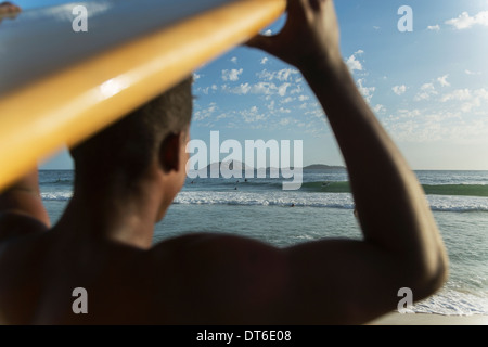 Close up of young man carrying surfboard, Rio De Janeiro, Brazil - Stock Photo