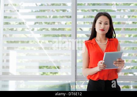 Portrait of businesswoman holding digital tablet - Stock Photo