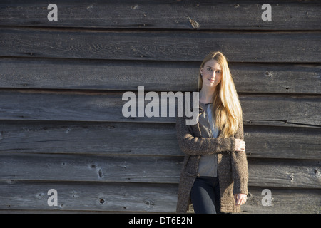 A young woman leaning against the wooden wall of a barn wearing a long knitted coat. - Stock Photo