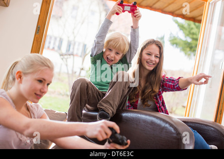 Teenage girls and boy playing games console - Stock Photo