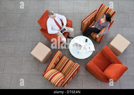 Overhead view of interview in office atrium - Stock Photo