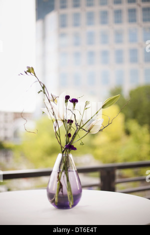A table on a terrace in the city. A vase of flowers. Small purple flowers, and white lily and orchid blooms. - Stock Photo