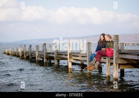 Teenage girls sitting on jetty - Stock Photo