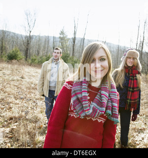 A group of three people, a man and two women, on a walk on a winter day. - Stock Photo