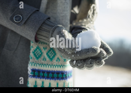A young woman holding a small snowball in her gloved hands. - Stock Photo