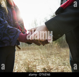 A couple in winter coats, outdoors on a winter's day. Holding hands. - Stock Photo