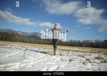 A man in a cable knit jumper and muck boots standing with his arms stretched out, in a snowy rural landscape. - Stock Photo