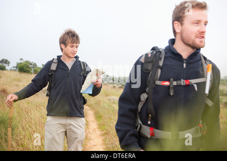Two male hikers with backpacks and map - Stock Photo